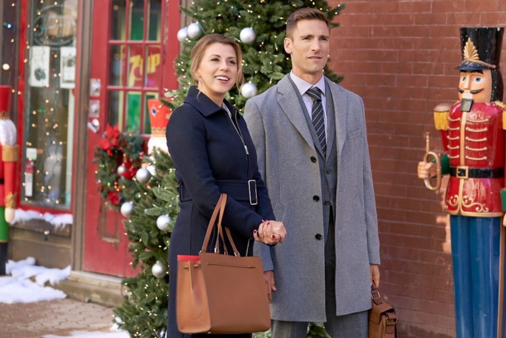 """Jodie Sweetin in """"Merry and Bright"""" wearing blue winter coat and tan bag"""